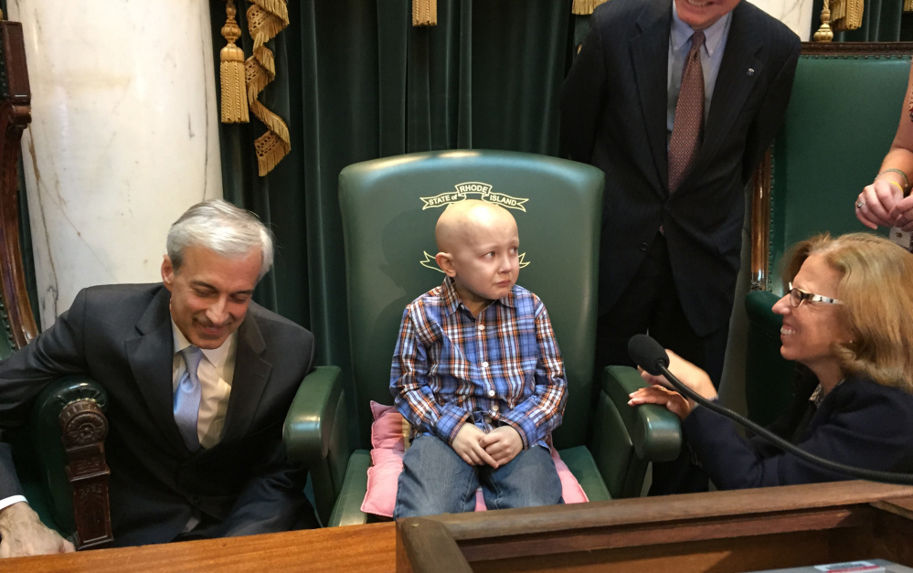 """Dorian Murray, 8, of Westerly, R.I., is a bit overwhelmed as he sits in the Statehouse Senate Chamber in Providence, R.I., Wednesday, Jan. 20, 2016 as he is honored by Rhode Island lawmakers, from left, Majority Leader Dennis Algiere, State Rep. Brian Kennedy and Senate President Teresa Paiva Weed, who proclaim it """"#DSTRONG Day"""" in a general assembly resolution. Murray, who has a rare and untreatable form of pediatric cancer, has said his final wish was to become famous in China."""