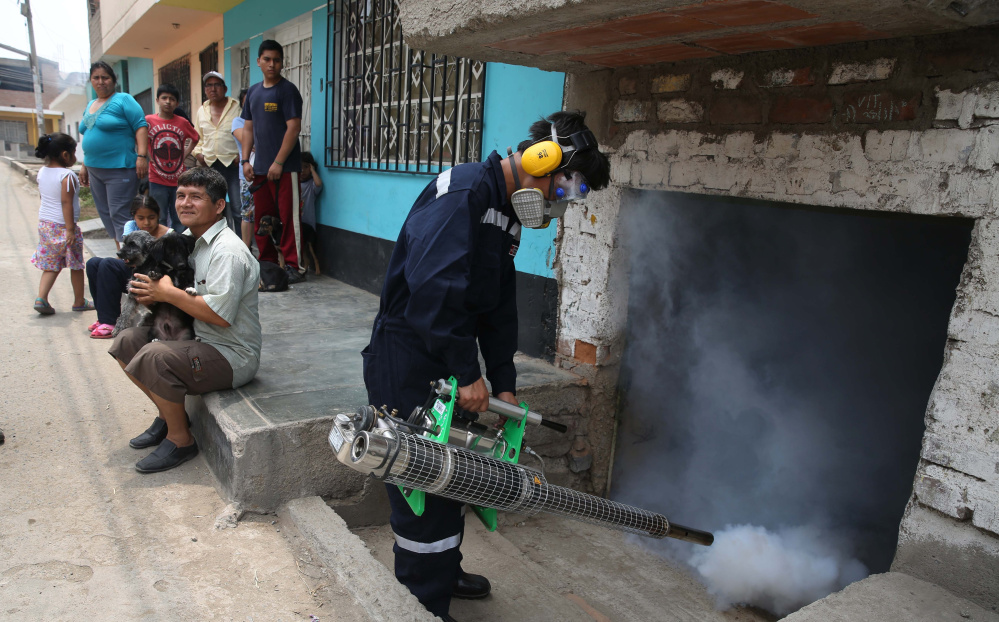 A health worker in Lima, Peru, fumigates on Friday against the mosquito that carries the Zika virus. Though it causes only a mild illness in most people, some reports link it to a birth defect with a smaller head size.