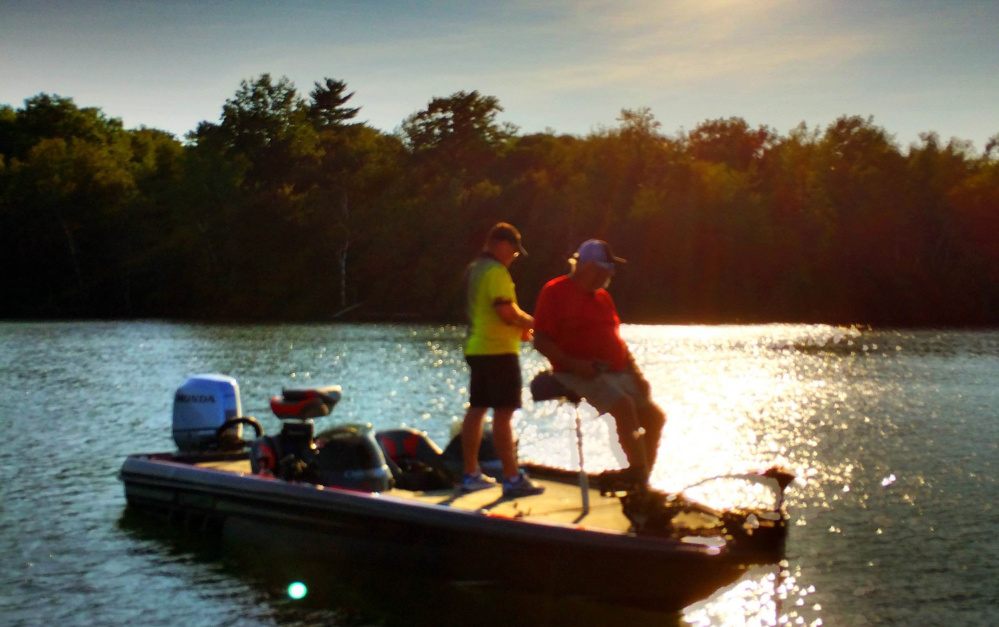 """Ted Thibault, of the fishing equipment firm Tuf-Line, and Charlie Ingram, from the Outdoor Channel show """"Fishing University,"""" cast their lines during a September sunset on China Lake while shooting an episode of the show. The episode airs this weekend."""
