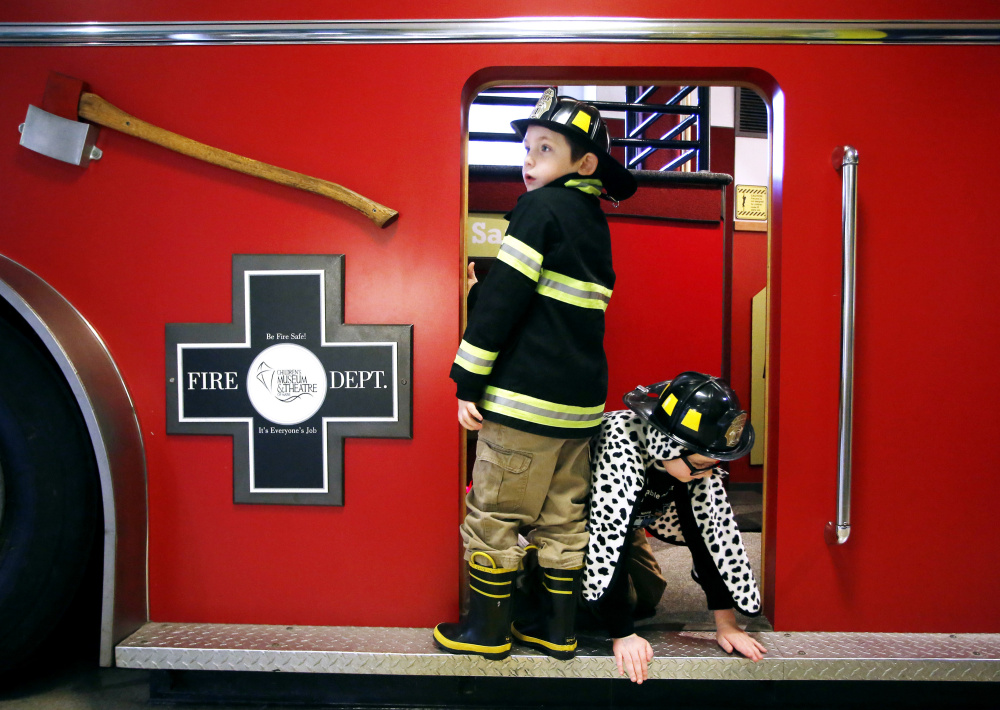 Jack Donovan, 6, left, of Scarborough and his brother Joey, 9, play on a firetruck exhibit. Derek Davis/Staff Photographer