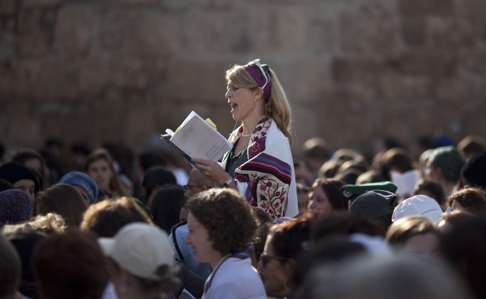 A Jewish woman wears a prayer shawl as she prays at the Western Wall, the holiest site where Jews can pray in Jerusalem's Old City.