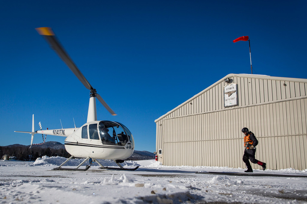 Kevin Coates of Battle Ground, Washington, a member of Native Range Capture Services, runs to a helicopter with moose collars in his hand while working with the Maine Department of Inland Fisheries and Wildlife on a moose study.
