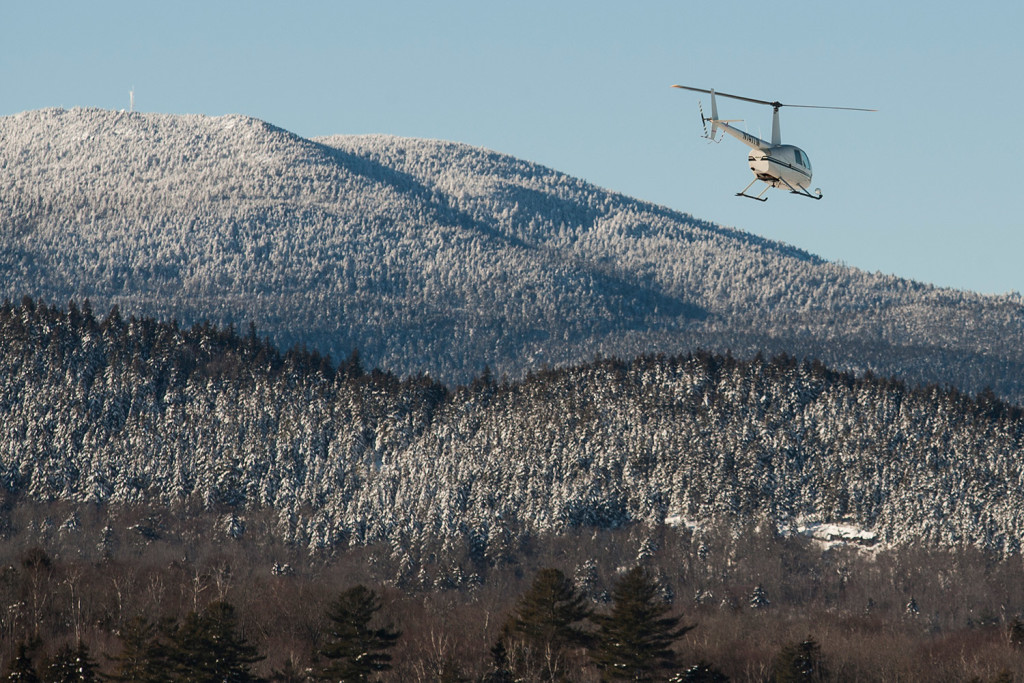 A small helicopter carrying a team from Native Range Capture Services passes by Big Moose Mountain outside Greenville on its way to place GPS collars on moose.