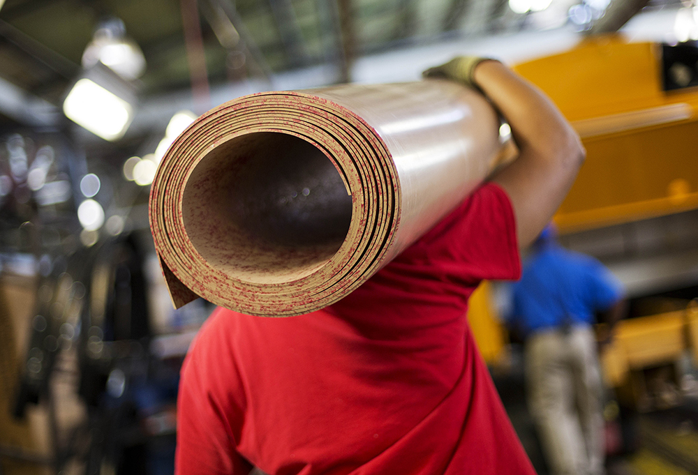 A worker carries a roll of sub flooring to be installed in a school bus on an assembly line at Blue Bird Corp.'s manufacturing facility, in Fort Valley, Ga. Some businesses said that efforts to reduce stockpiles of goods have also held back orders. The Associated Press