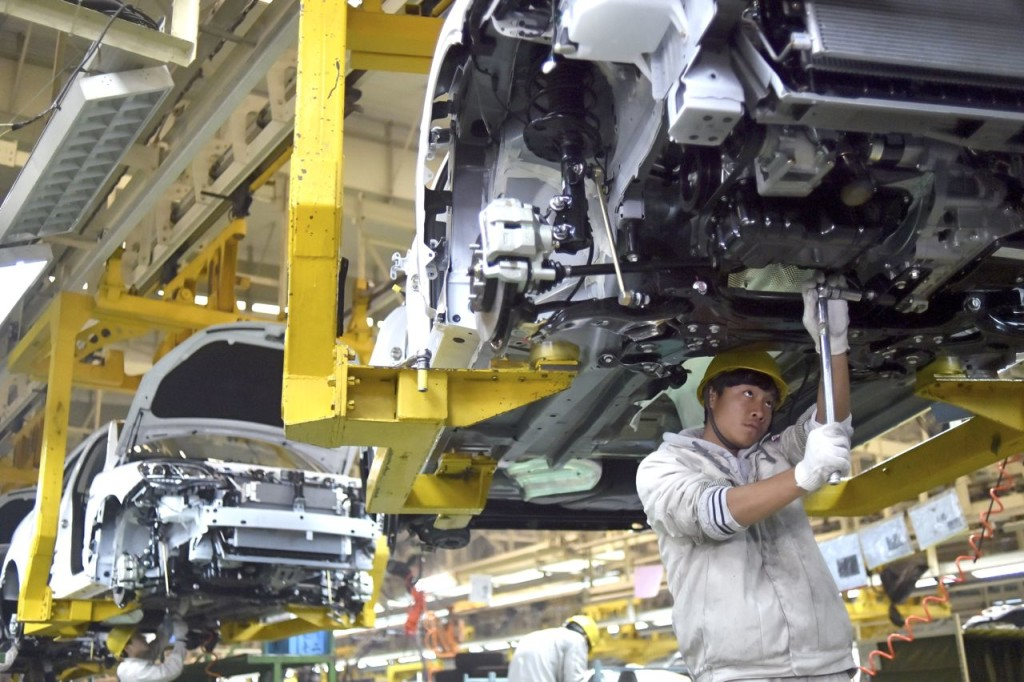 A worker labors on the assembly line of the X5 SUV of Zotye Auto in Hangzhou in China's Zhejiang province. China's economic growth edged down to 6.8 percent in the final quarter of 2015 as trade and consumer spending weakened.Chinatopix via AP