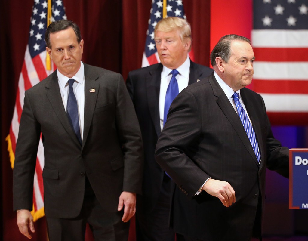 Donald Trump appears on stage with Republican candidates Rick Santorum, left, and Mike Huckabee at Trump's event Thursday night. Santorum and Huckabee had participated earlier Thursday night in the preliminary Republican debate in Des Moines.