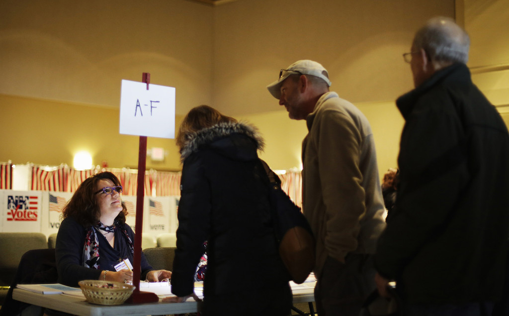 Paula Dobens, an assistant election official, left, helps voters lining up to cast their ballots at a polling place for the New Hampshire primary, Tuesday in Nashua, N.H. The Associated Press