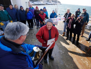 """Nick Mavadones of Casco Bay Lines presents Chester Pettengill with a plaque with a liberty bell for his service to Cliff Island. """"Chester is the spirit of Cliff Island,"""" one resident said."""