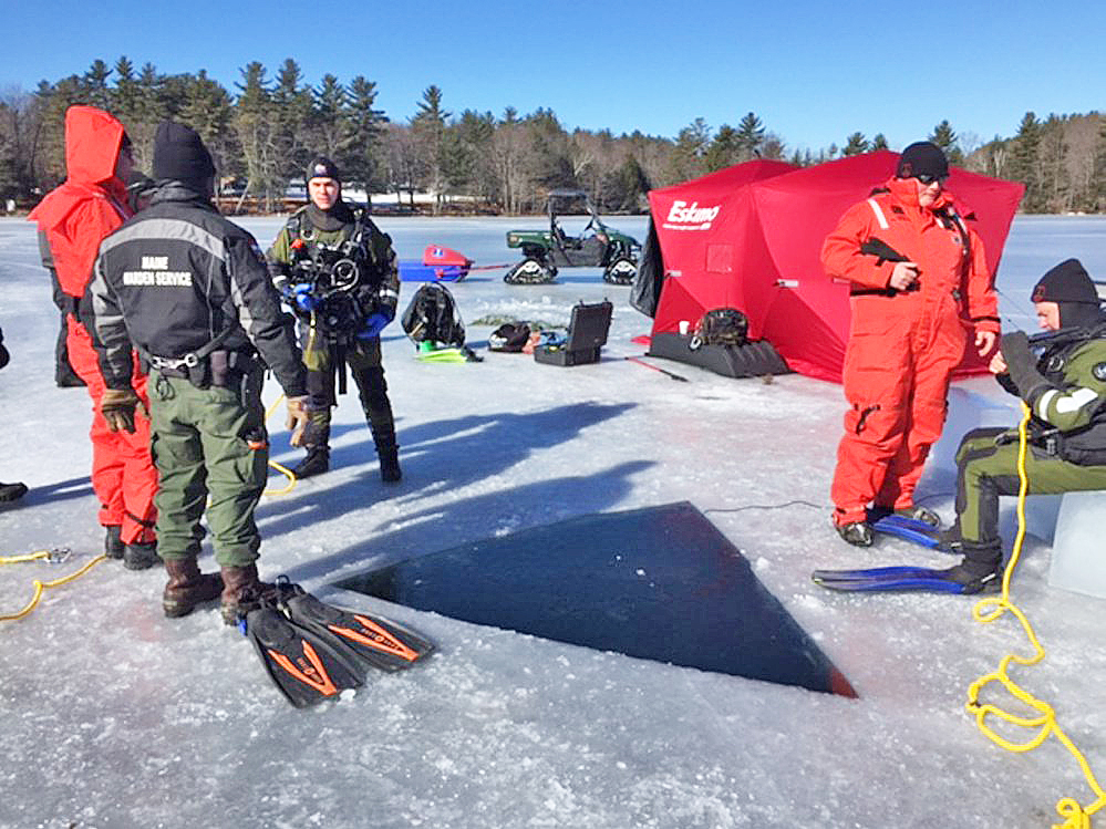 Maine Game Warden divers prepare to enter the water Monday on Salmon Lake in North Belgrade in search of an all-terrain vehicle.