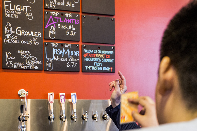 Lea Romanowsky, a tasting room ambassador at Rising Tide, points to the breweries board of beer selections as Lauren Ramirez,, 23, of Boston, has her credit card out ready to make her selection at the newly expanded tasting room.