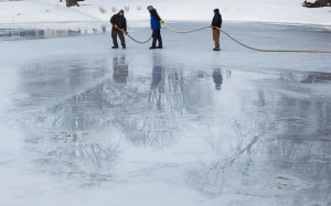 Will Faustman, left, Dwayne O'Roak, center, and Paul Cobb from the South Portland Parks Department spray water on the Mill Creek Park pond to smooth out the ice for ice skating.