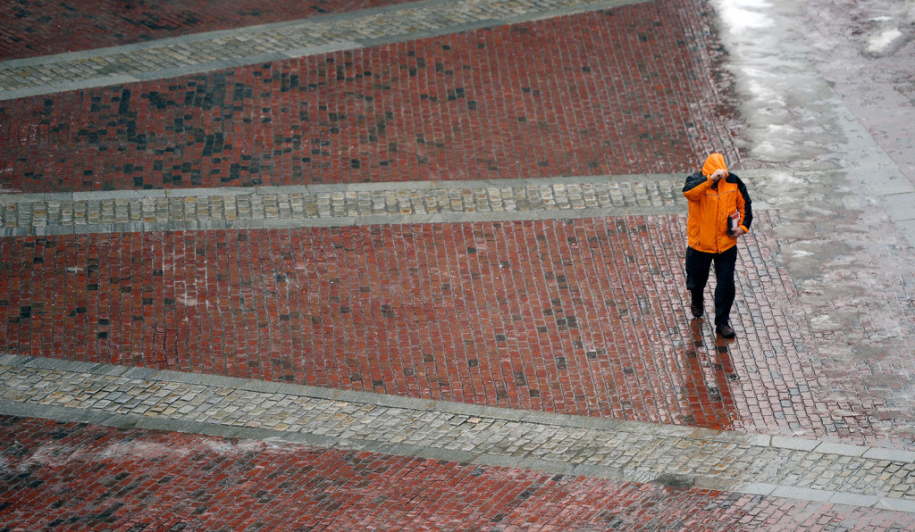 A pedestrian holds his hood in place as the wind blows while he walks through Monument Square in Portland Tuesday. Shawn Patrick Ouellette/Staff Photographer