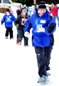 Jaimi Buck of Work First in Farmington strides to a win in her 50-meter snowshoe time trial at the 2016 Special Olympics Maine Winter Games at Sugarloaf on Monday. At far left is team member Noele Brown.