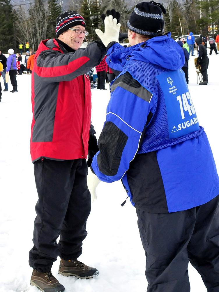 Dave Baird, formerly of Winslow and a volunteer for the Special Olympics Maine Winter Games for the past 30 years, congratulates athlete Jaimi Buck during snowshoe races at Sugarloaf on Monday.