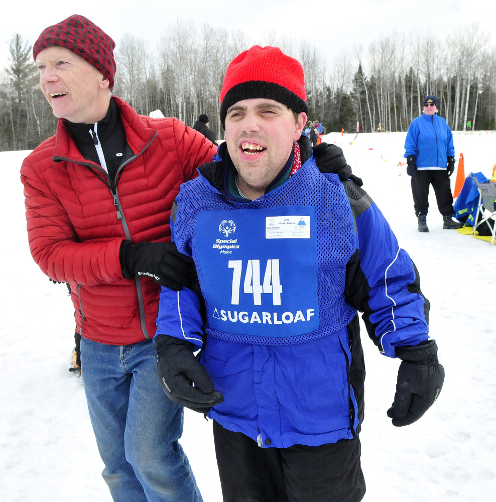 Work First's Mark Gordon is assisted by Randy Judkins after the 100-meter snowshoe race. Other competitions are in alpine and Nordic skiing and speed skating.