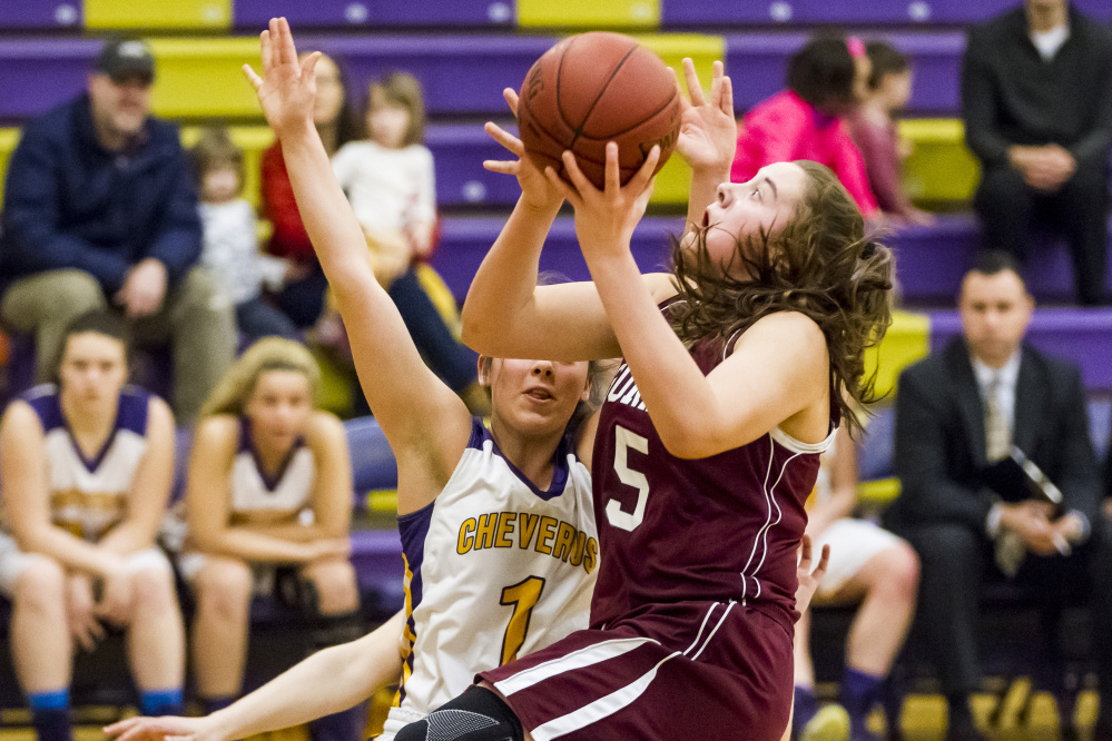 Mackenzie Holmes, the freshman center who's so hard to stop for Gorham, drives against Alayna Briggs of Cheverus. Holmes collected 20 points in a 64-36 victory on the road.