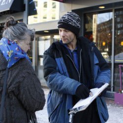 Brandon Scott speaks with Joyce Lorraine on Jan. 21 as he collected signatures on a York County casino referendum petition in Portland's Monument Square. Paid $7 to $10 per name, circulators carried out an aggressive campaign that often skirted the truth.