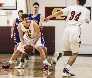 Justin Guerette of Cape Elizabeth keeps an eye on teammate Nate Ingalls before passing Tuesday night. Tyler Gee, behind Guerette, and Sam Skop defend for Falmouth, which collected a 44-42 victory on the road.