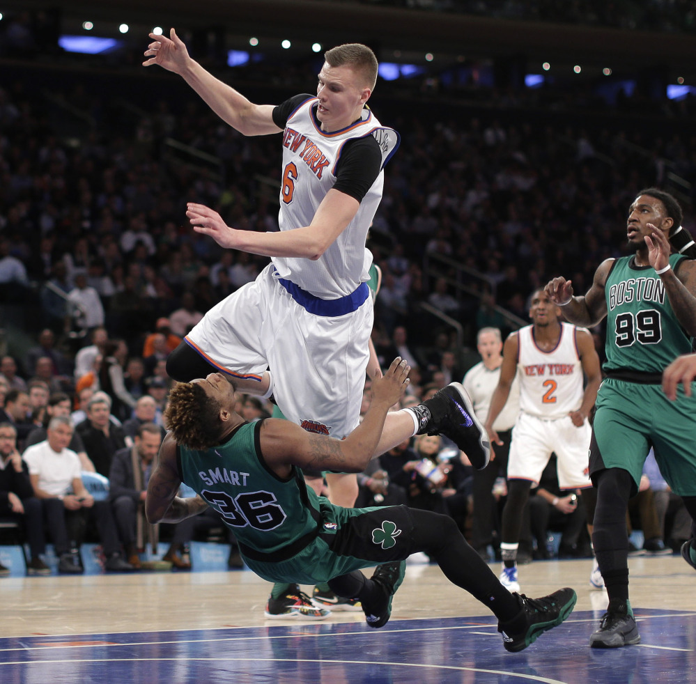 Celtics guard Marcus Smart takes the charge from Knicks forward Kristaps Porzingis in the first quarter. Porzingis was called for an offensive foul on the play.