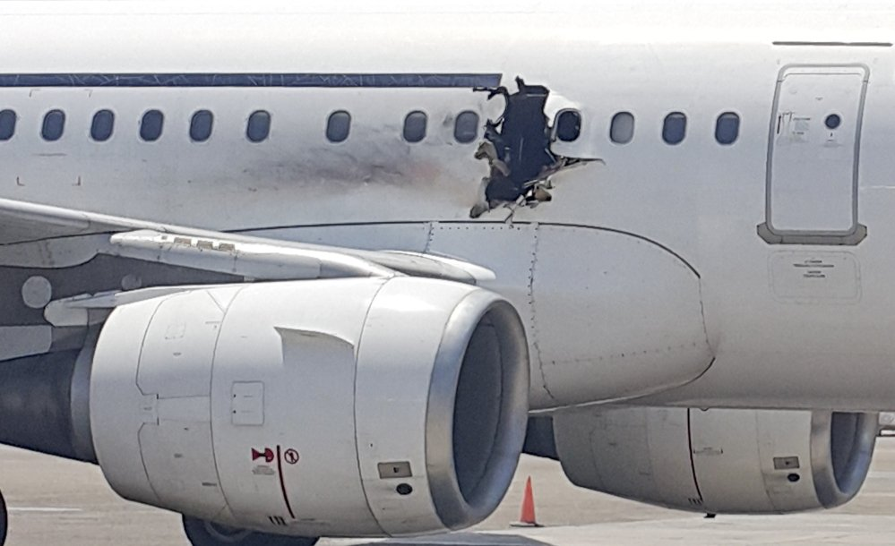 A hole is photographed in a plane operated by Daallo Airlines as it sits on the runway of the airport in Mogadishu, Somalia.