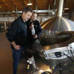Todd Usry, front, chief of Breckenridge Brewery, checks over beer brewing in the company's factory in Littleton, Colo. The entry of Anheuser-Busch InBev into Colorado's craft beer paradise has some brewers worried that the world's largest brewer could squeeze independent makers out of the booming industry. (AP Photo/David Zalubowski)