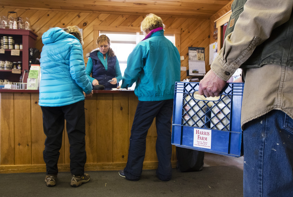 A customer waits to purchase milk as Rachel Harris waits on cross-country ski customers.