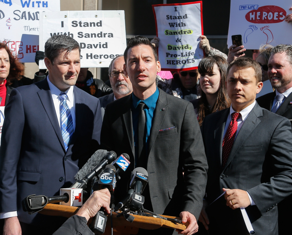 David Daleiden, center, an anti-abortion activist indicted last week in Houston, speaks to the press on Thursday. He plans to reject a plea deal that would essentially get him probation for tampering with a governmental record.