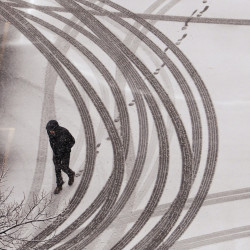 A man walks over tracks in a Portland parking lot coated in snow Friday.