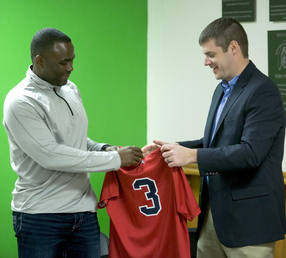 Portland Sea Dogs General Manager Geoff Iacuessa, right, hands new Manager Carlos Febles a team jersey Friday at Hadlock Field. Derek Davis/Staff Photographer