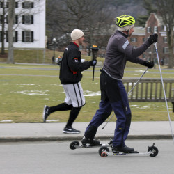 David McCrillis, right, on roller-skis and Garrett Hubert, center, carrying the torch, set off Friday, Feb. 5, 2016, from the Dartmouth Outing Club in Hanover, N.H., for the 30-mile trek to the Newport town common to launch the 100th Newport Winter Carnival. They are following the path that McCrillis's grandfather, carnival founder and Dartmouth College student John McCrillis, strapped on cross-country skis to make the journey to the first carnival in 1916. Organizers believe it is the oldest continuously run town winter carnival in the country. (AP Photo/Lynne Tuohy)
