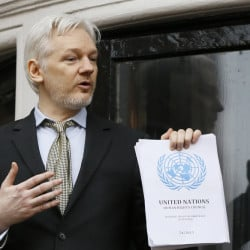 Wikileaks founder Julian Assange holds a U.N. report issued Friday that says he has been arbitrarily detained in the Ecuadorean Embassy in London.