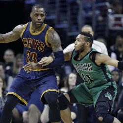 Cleveland's LeBron James backs down Boston's Evan Turner in the first half of the Celtics' 104-103 win Friday in Cleveland.