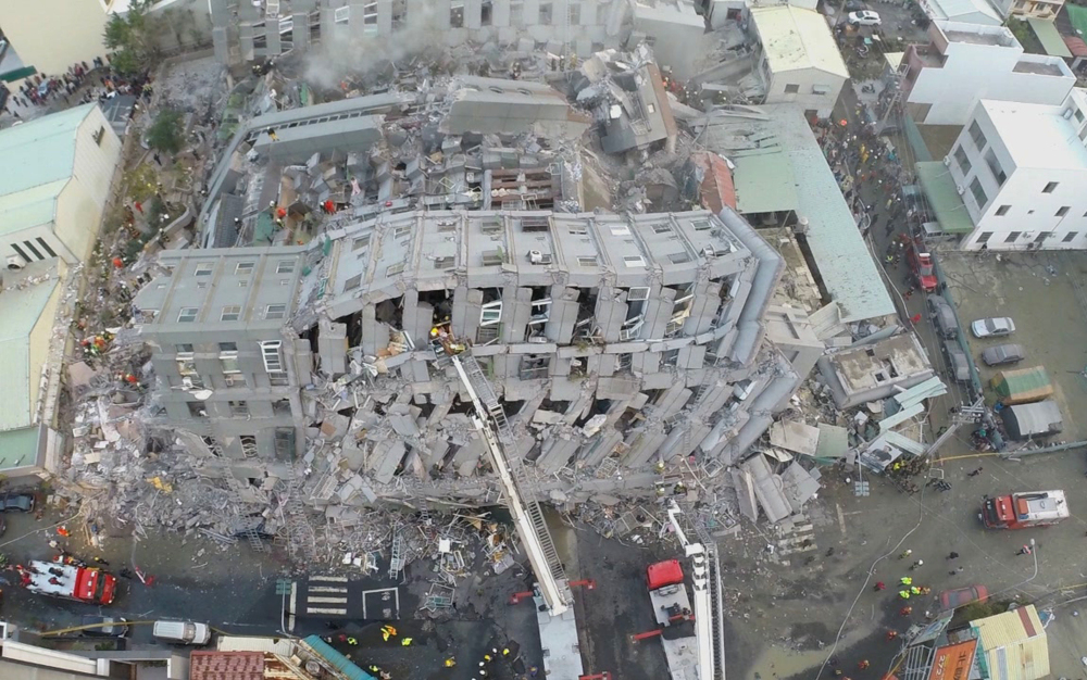 In this photo taken from a drone mounted camera, rescue workers search a collapsed building from an early morning earthquake in Tainan, Taiwan, on Saturday.