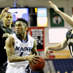 UMaine's Aaron Calixte drives the lane against UMBC's Jairus Lyles and Joel Wincowski in the first half Saturday at the Portland Expo.