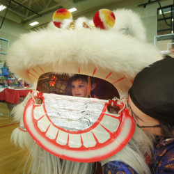 WESTBROOK, MAINE - FEBRUARY 6: Rodger Wong, right, helps Will Lindecamp, 3, try on a lion's head in the gymnasium at Westbrook Middle School during a Chinese New Year celebration sponsored by the Chinese and American Friendship Association of Maine and the Confucius Institute of the University of Southern Maine on Saturday, February 6, 2016. (Photo by Gregory Rec/Staff Photographer)