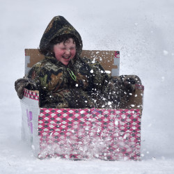 A competitor in the Box Sled Derby Race zips through a spray of snow Saturday at the annual Winter Carnival at Lake George Regional Park in Skowhegan.