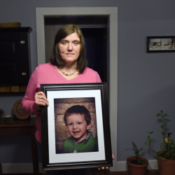 Shot and wounded herself by an abusive ex-husband who then committed suicide, Hollie Ayers poses with a photograph of her late son, Michael, 2, who was slain during the 2013 rampage at her home in Bedford, Pa.