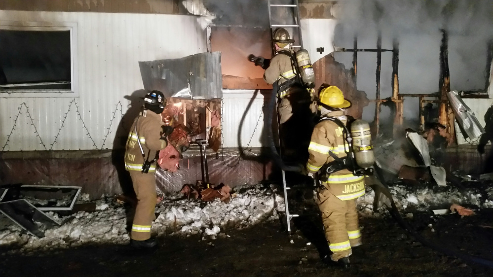 Firefighters hose down a mobile home that erupted in flames early Saturday morning on Webb Road in Oakland. The fire destroyed the home and injured two of its four occupants.
