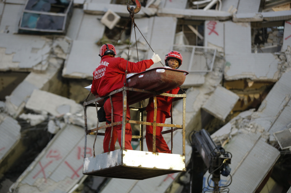 Emergency workers carry a victim recovered from a collapsed building in Tainan, Taiwan, on Sunday. Rescuers found more signs of life in the wreckage of a high-rise apartment building that collapsed in a powerful earthquake in southern Taiwan.