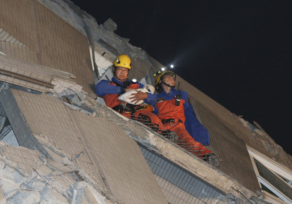 Rescue workers carry a baby swaddled in a cloth from the rubble of a toppled building after an earthquake in Tainan, Taiwan, Saturday.