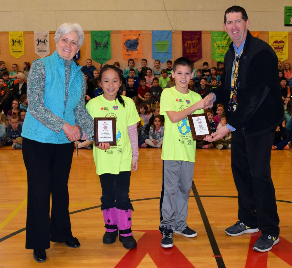 Wells Elementary School Principal Marianne Horne, left, and Assistant Principal Ken Spinney present recognition plaques to fourth-graders Maya Grainger and Colton Harding for their first-place finishes in the American Heart Association's 2015 Jump Rope for Heart fundraiser.