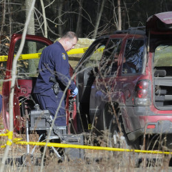 Maine State Police detectives examine the SUV containing the bodies of Eric Williams and Bonnie Royer, who were found dead on Sanford Road in Manchester early Christmas Day.