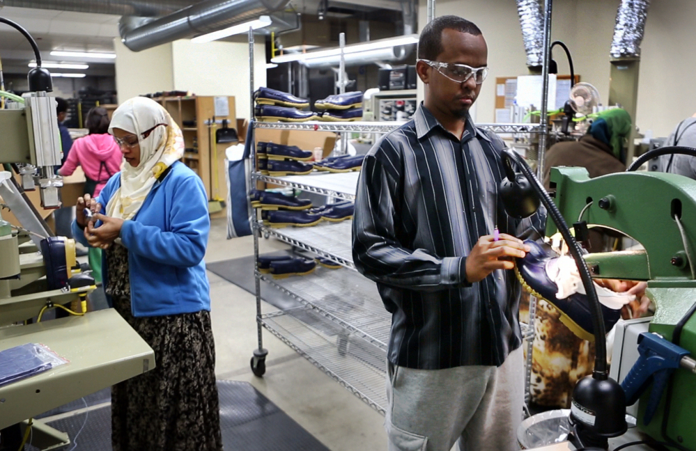 """Abdi Said, right, trims the rubber bottoms of Bean Boots at an L.L. Bean factory in Lewiston. Said, a refugee, was originally put in San Jose, California, before he moved cross-country to Lewiston. """"We are working hard and we're going to school and everything - like regular American people. They see that we are not different,"""" he said."""