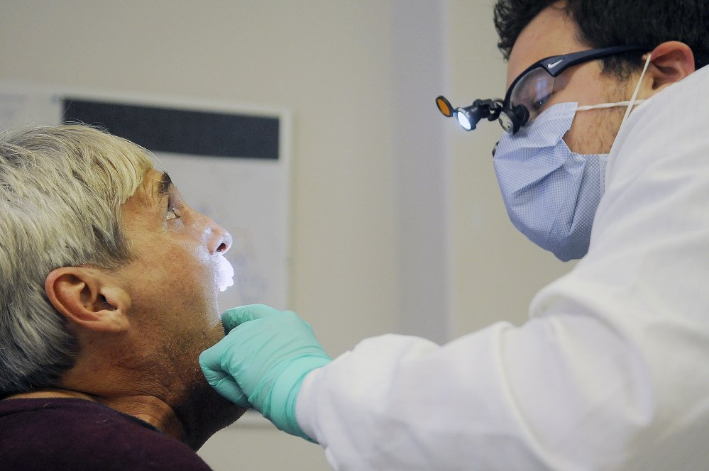 Dentist Ryan Harrington examines Geno Toppi of Augusta during the 17th annual Homeless Veterans Stand Down at the Togus VA Medical Center on Oct. 18, 2014. Only half of the Maine veterans who have applied for care under a program to streamline access to health providers have been able to get an appointment.