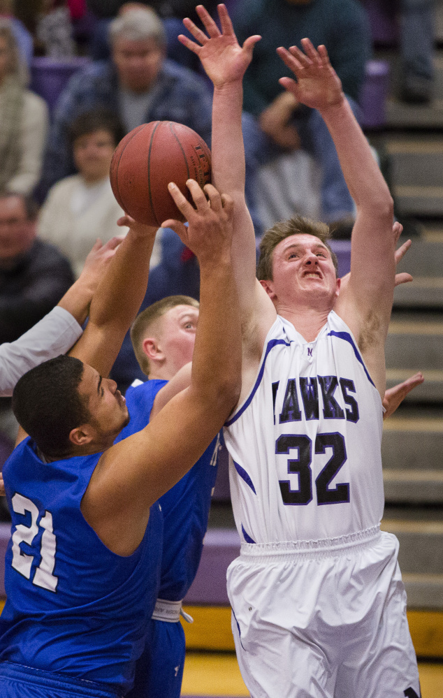 Ben Beers of Marshwood, right, and Travon Bradford of Kennebunk compete for a rebound Tuesday night during their Class A South boys' basketball prelim. Marshwood advanced to the quarterfinals against No. 1 Greely with a 63-54 victory.