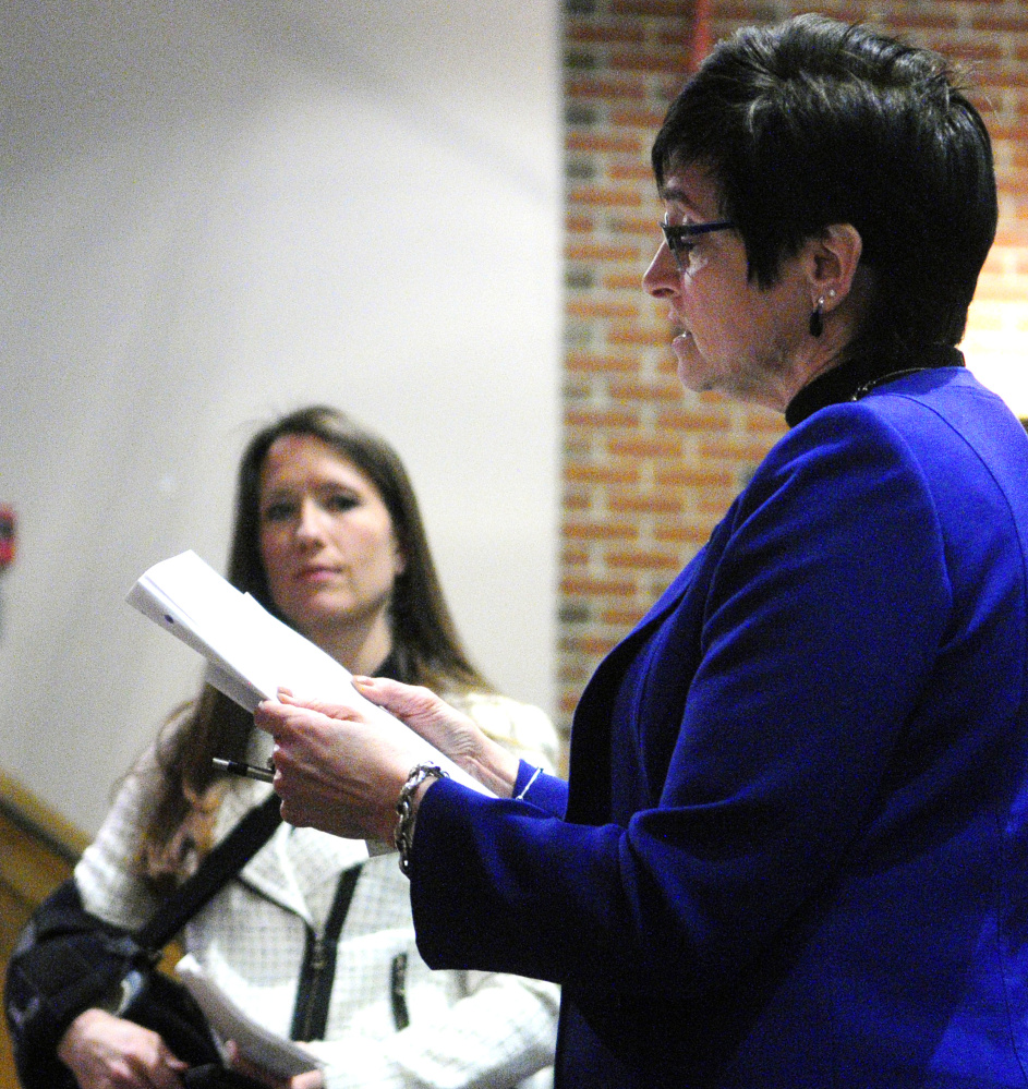 Rep. Gay Grant, D-Gardiner, reads from Gov. Paul LePage's State of the State letter while asking him a question Tueday evening during a town hall-style meeting at Hall-Dale High School in Farmingdale.