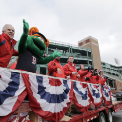 The Boston Red Sox new mascot Tessie the Green Monster, second from left, rides on the back of a truck with team ambassadors leading the team's equipment truck, behind right, as the equipment truck departs Fenway Park in Boston, Wednesday, Feb. 10, 2016, en route to the team's spring training baseball facility in Fort Myers, Fla. (AP Photo/Steven Senne)