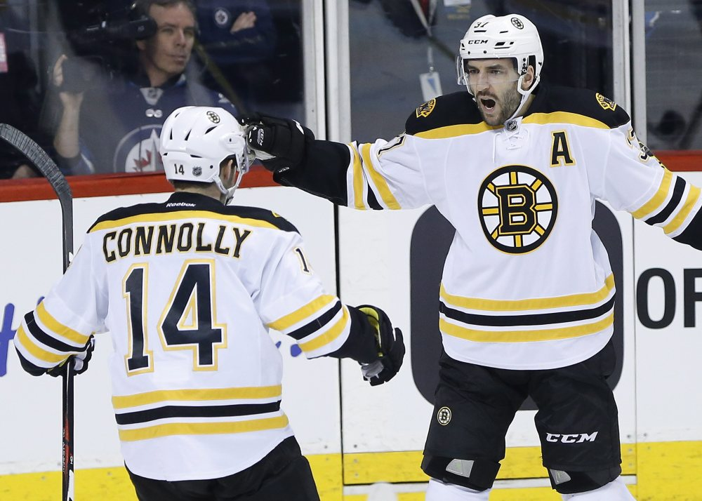 The Bruins' Brett Connolly (14) and Patrice Bergeron celebrate Bergeron's goal early in the first period Thursday night in Winnipeg, Manitoba. Bergeron scored two goals in the Bruins' win.
