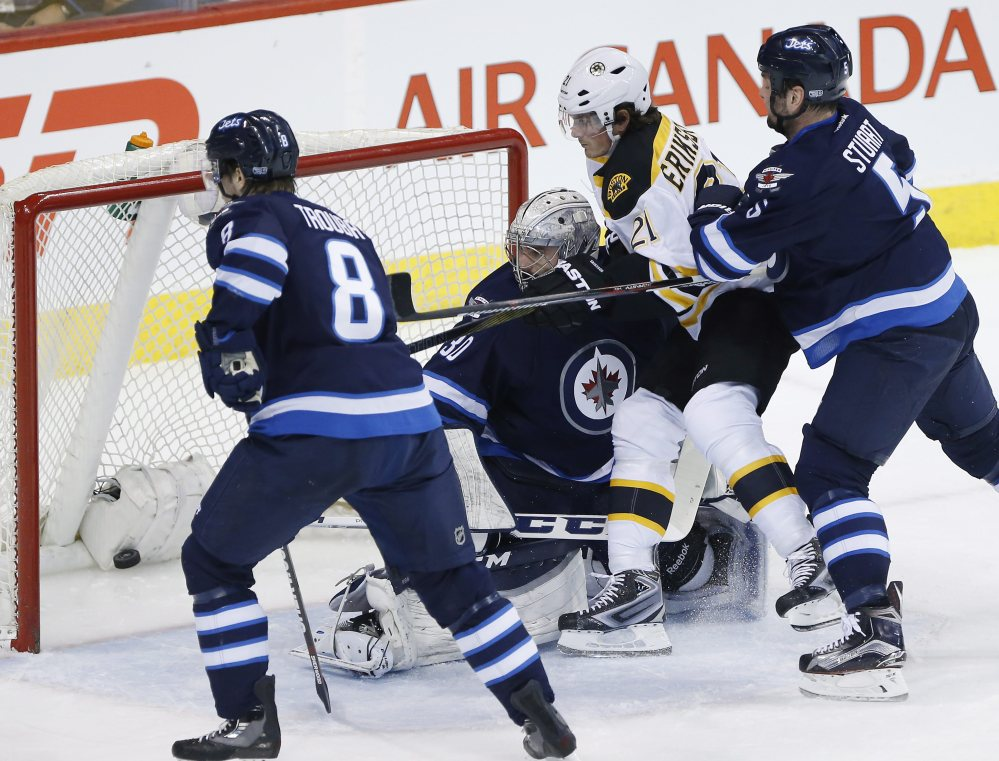 The Bruins' Loui Eriksson scores on Winnipeg goaltender Connor Hellebuyck in the first period.