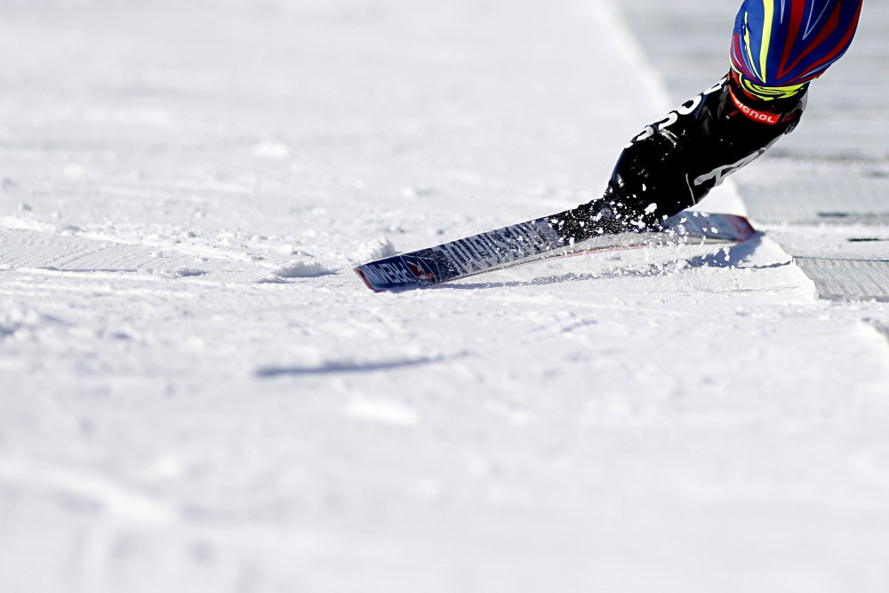 Snow flies as a competitor sprints off the shooting mat during the 10-kilometer men's sprint Thursday.
